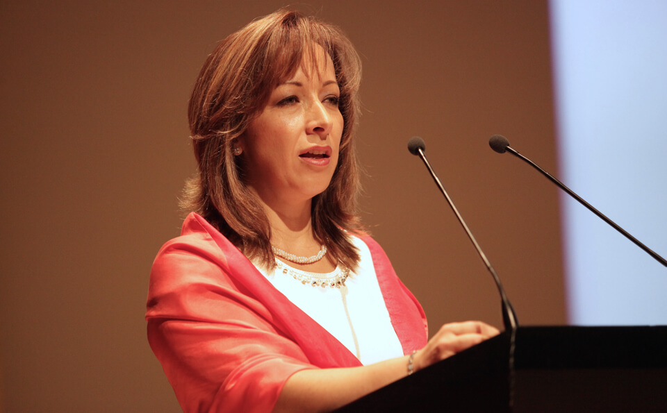 una mujer de chaqueta color salmón habla frente a un micrófono