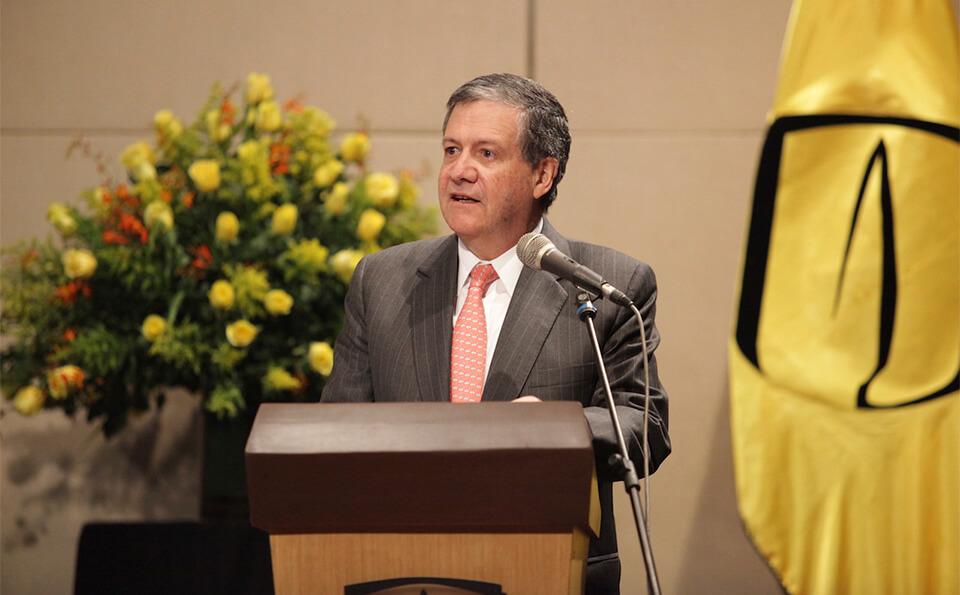 vemos a un hombre mayor dando un discurso en un auditorio, se ven atrás unas flores y la bandera de la universidad de los andes