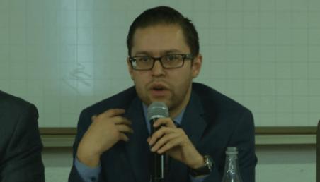 hombre con gafas habla al micrófono sobre la marihuana medicinal