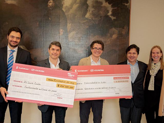 Cuatro directivos de las empresas Colpatria y Universidad de los Andes sostienen cheque de donación