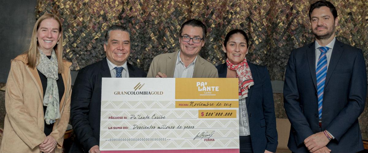 Directivos de Uniandes y de Gran Colombia gold posando frente a cheque gigante