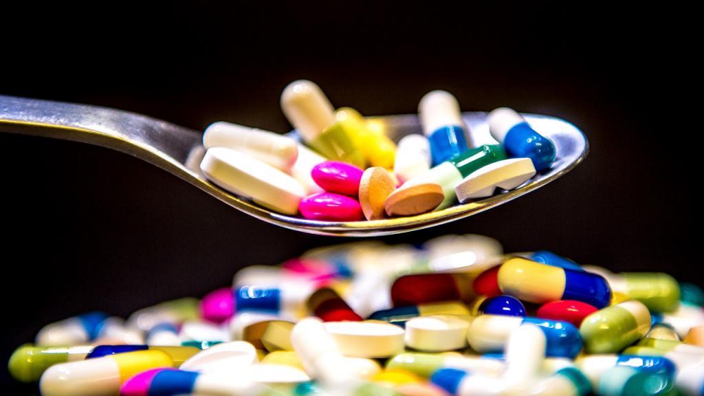 Una cuchara con cápsulas y pastillas