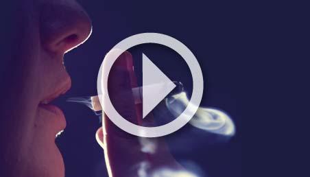 Mujer fuma y exhala el humo.