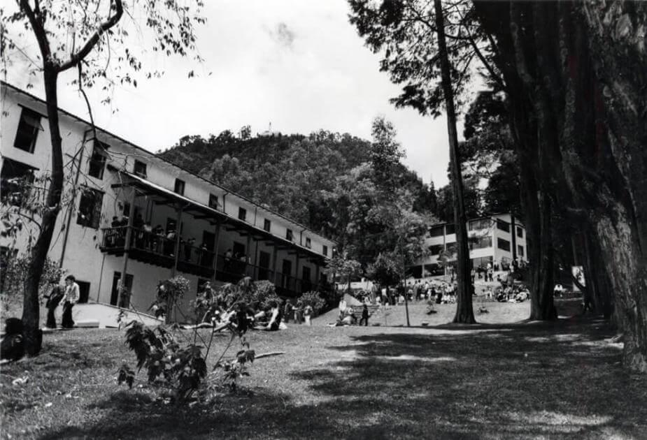 campus de la universidad de los andes, se ve un edificio blanco, un campo donde hay estudiantes sentados tomando sol  y muchos árboles