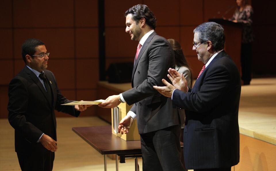 un hombre alto entrega diploma de grado a un hombre de traje negro