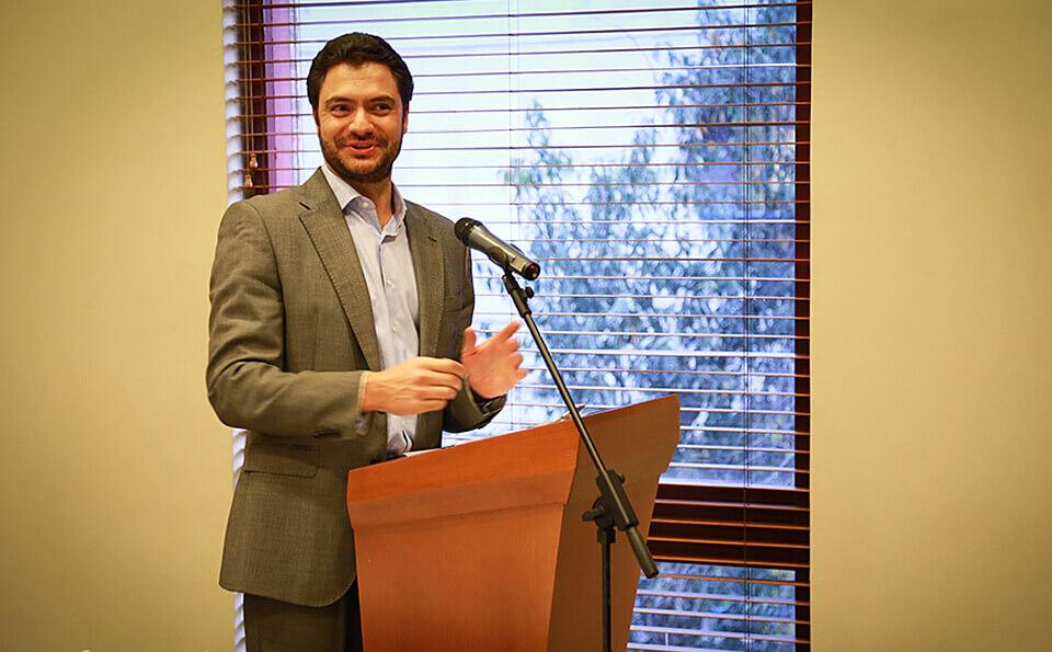 hombre de traje de pie al lado de un atril da discurso en evento