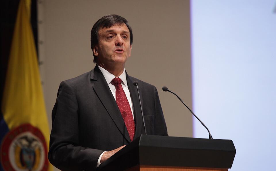 un hombre mayor de corbata roja está parado frente a un atril dando un discurso