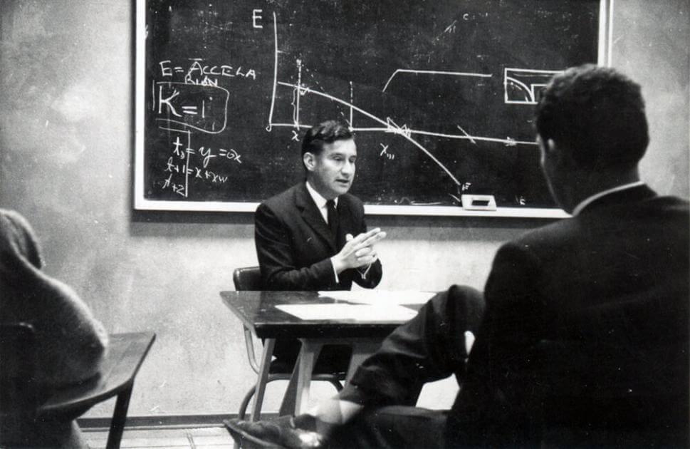 foto antigua en blanco y negro de un hombre en salon de clases, vemos la espalda de uno de sus alumnos