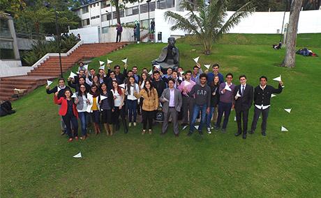 Grupo de egresados Uniandes en el prado Alberto Magno de la Universidad elevan sus manos en señal de saludo.