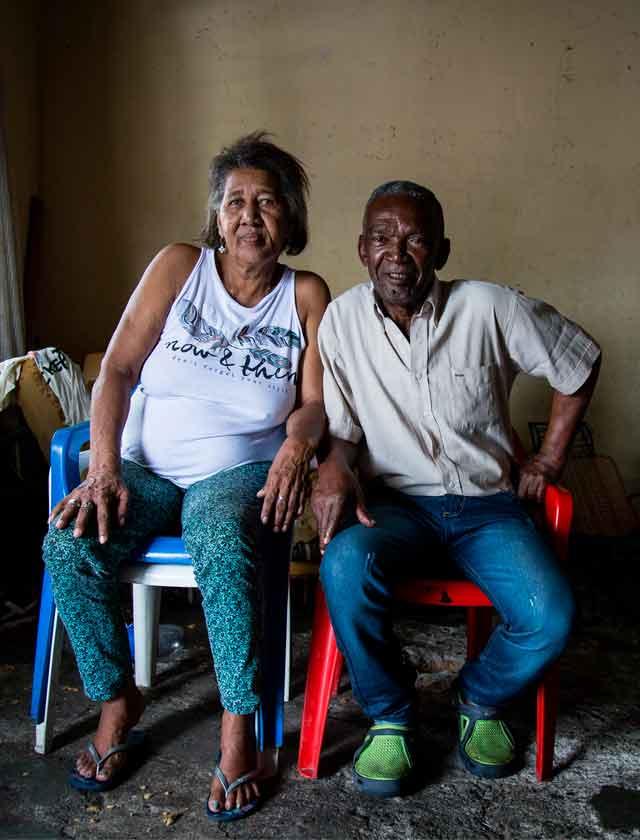 Dos ancianos en condición de pobreza sentados.