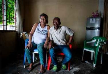 Dos ancianos de Barrancabermeja en condición de pobreza sentados en sillas.