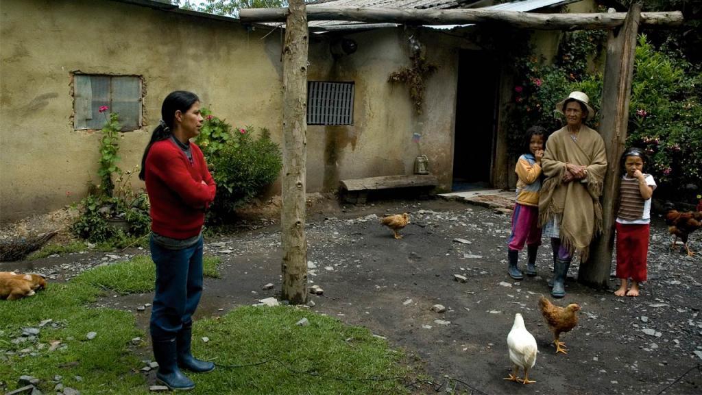 Una señora en la fachada de su casa. A pocos metros una abuela con dos niñas.