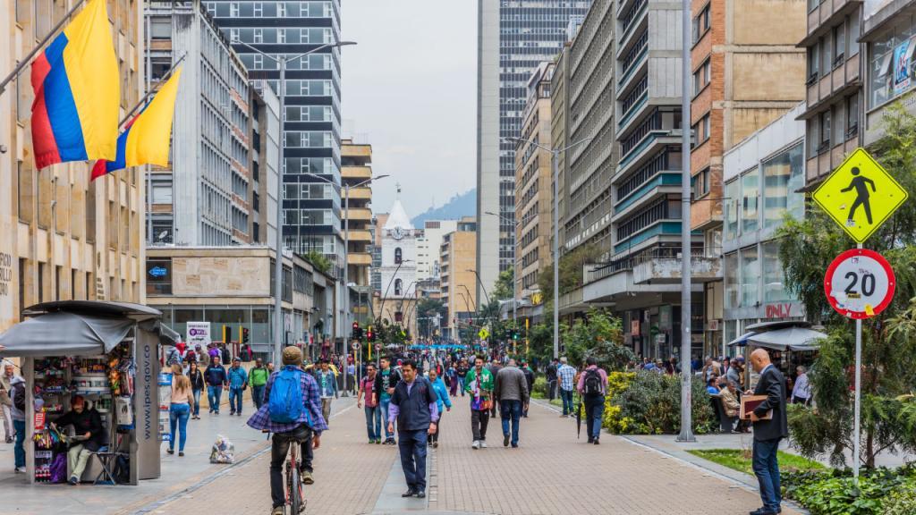 Calle bogotana, personas montando bici y caminando.