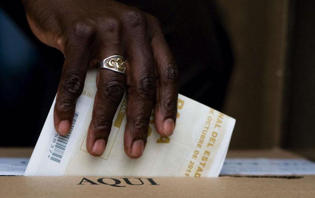Persona afrodescendiente deposita su voto en urna electoral colombiana