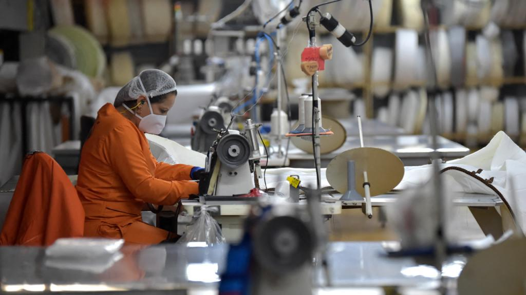 Mujer usa una máquina de coser industrial.