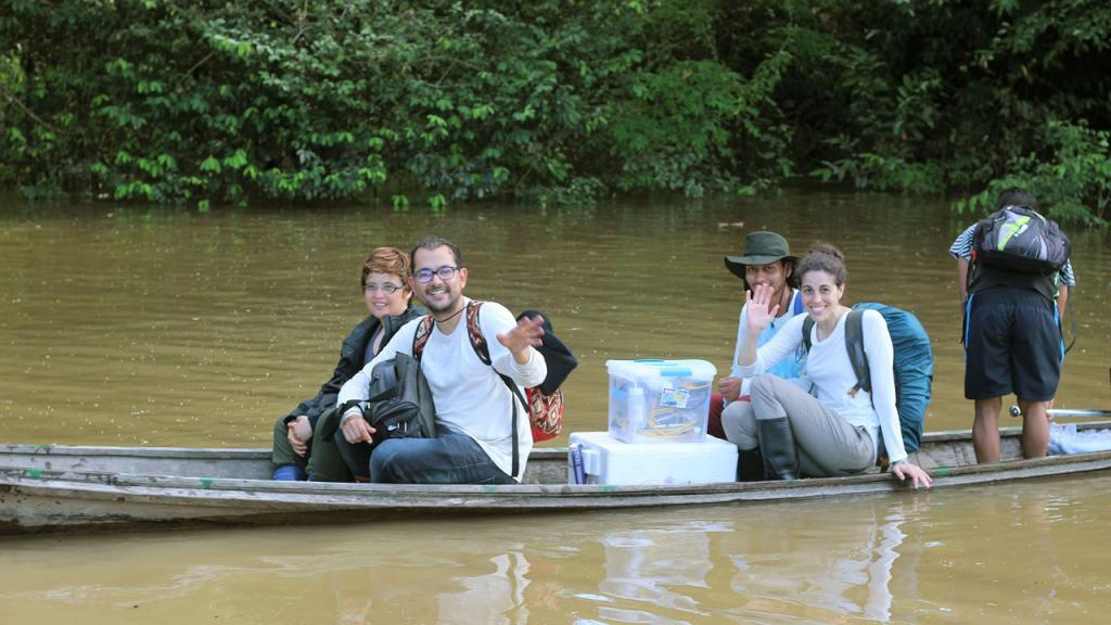 Cuatro personas navegan en una canoa por el río Amazonas