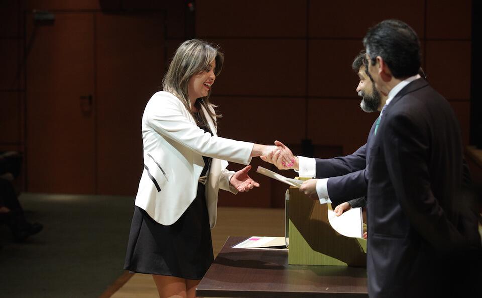 mujer de vestido negro y chaqueta blanca recibe diploma de manos de dos hombres