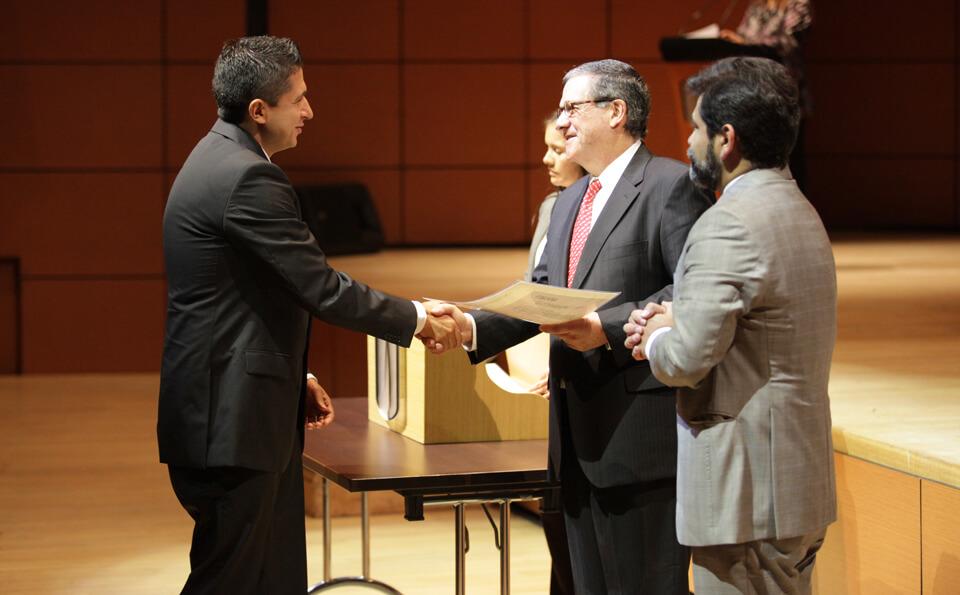 un hombre de gafas entrega diploma a un hombre de traje negro