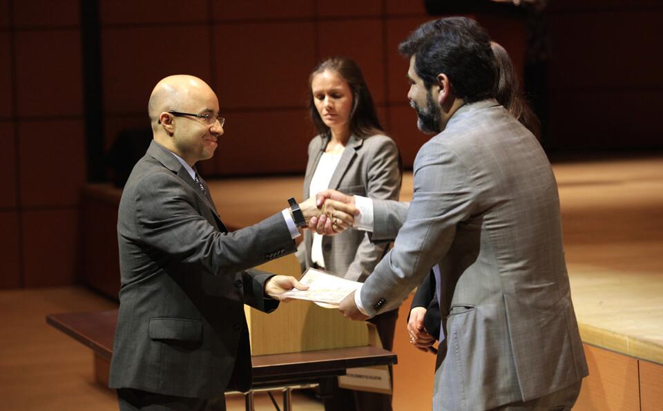 Un hombre calvo recibe diploma de un hombre de barba