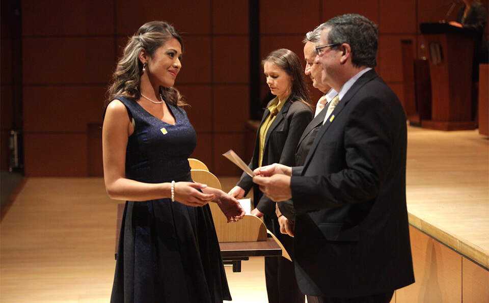 Vemos a una mujer de vestido negro y cabello largo en un auditorio, está recibiendo un diploma