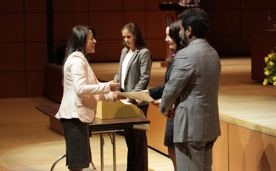 una mujer de chaqueta blanca recibe diploma de tres personas, dos de ellas mujeres