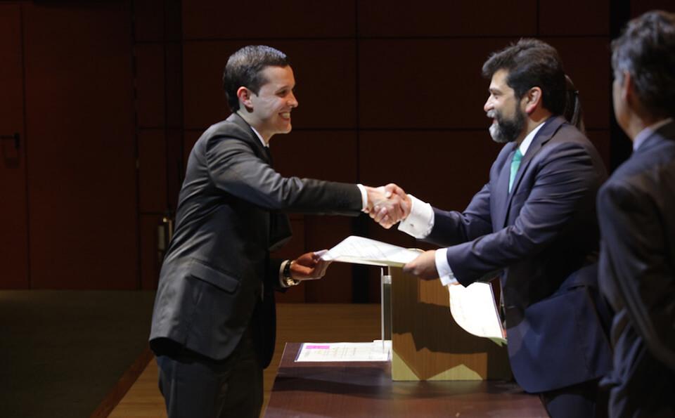 joven estrecha la mano de un señor mayor para recibir su diploma de grado