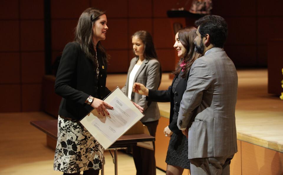 una mujer de chaqueta negra recibe diploma y da la mano a una mujer de vestido oscuro