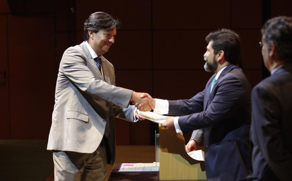 un señor de traje gris claro estrecha la mano de un señor que le entrega diploma de grado