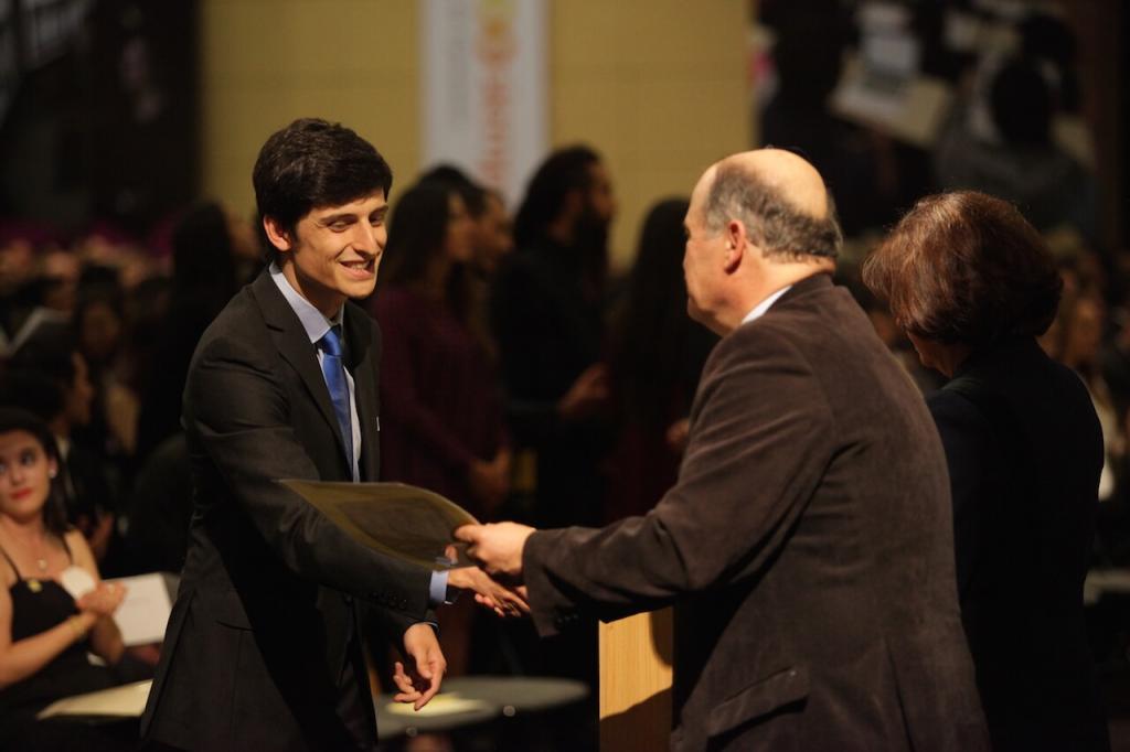 joven de corbata azul recibe diploma de grado