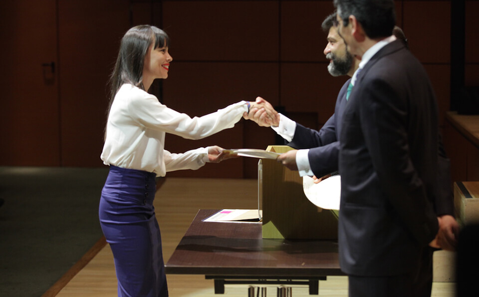 mujer de vestido azul y chaqueta blanca estrecha la mano de un hombre mayor en señal de agradecimiento al recibir diploma