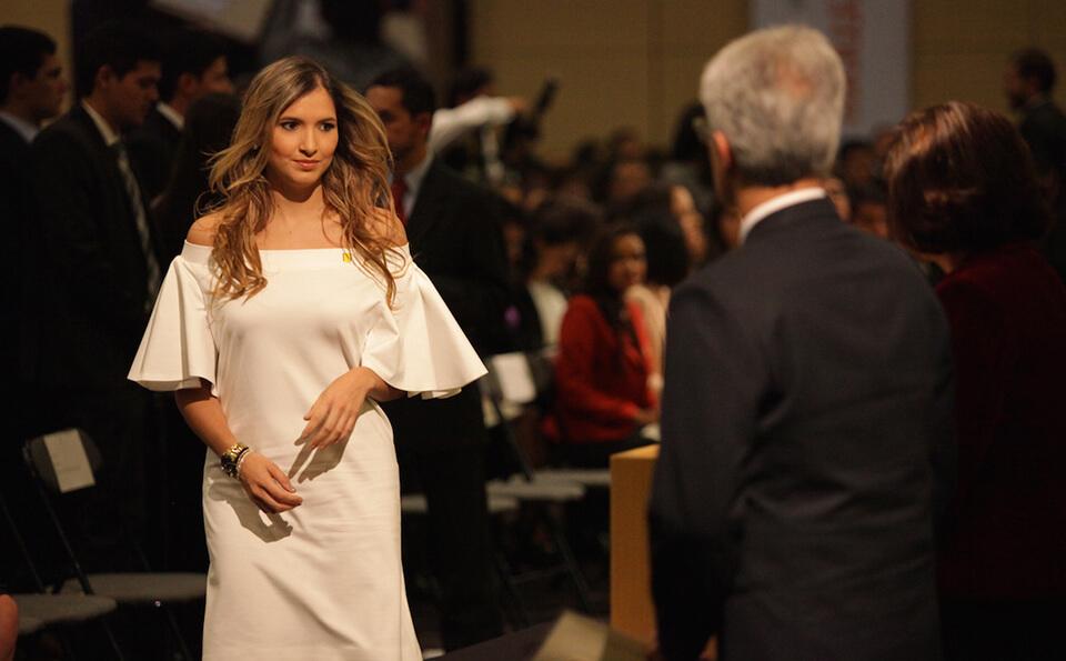 mujer rubia con vestido blanco se acerca a una mesa para recibir diploma de grado