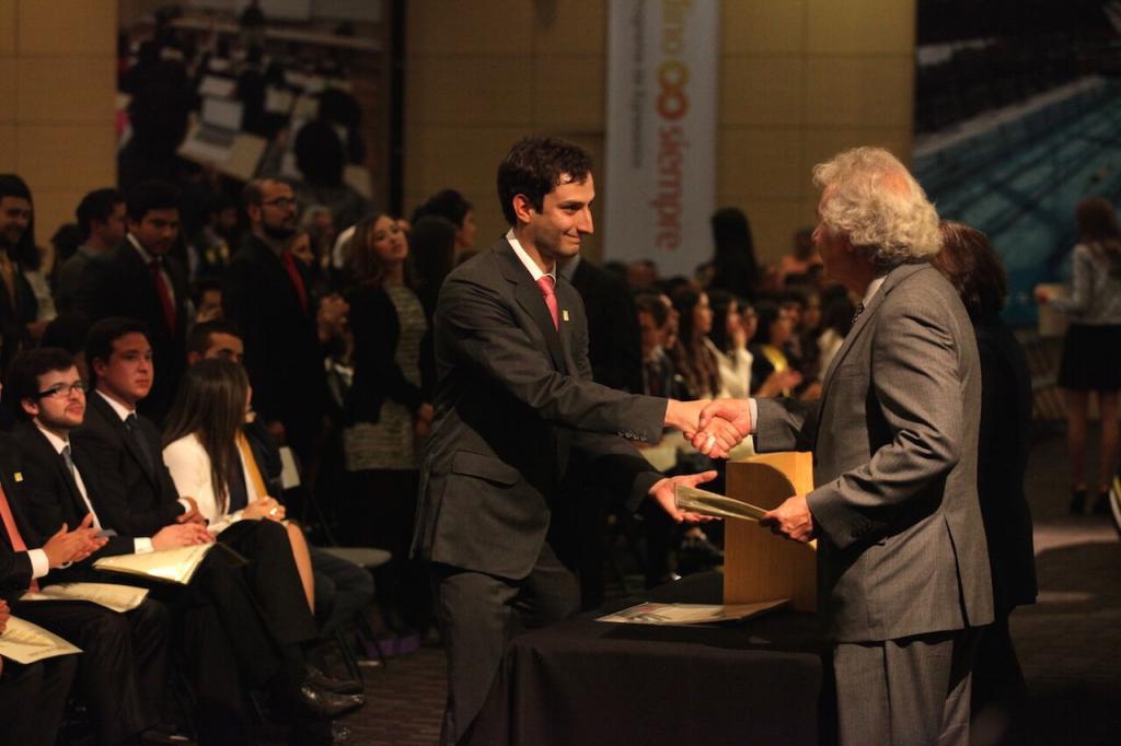 joven de traje recibe diploma y estrecha la mano de hombre canoso