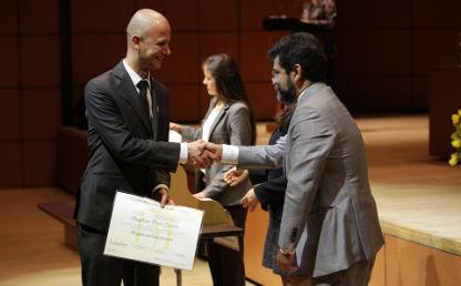 hombre alto recibe diploma y da la mano a un hombre con barba