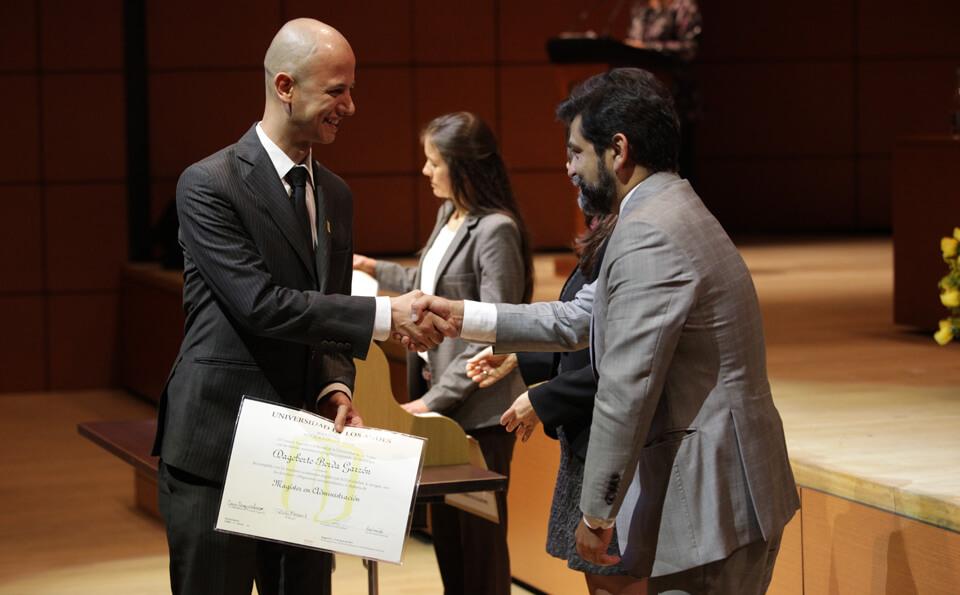 un hombre alto y calvo vestido de traje da la mano a un hombre con traje gris y barba que le entrega diploma