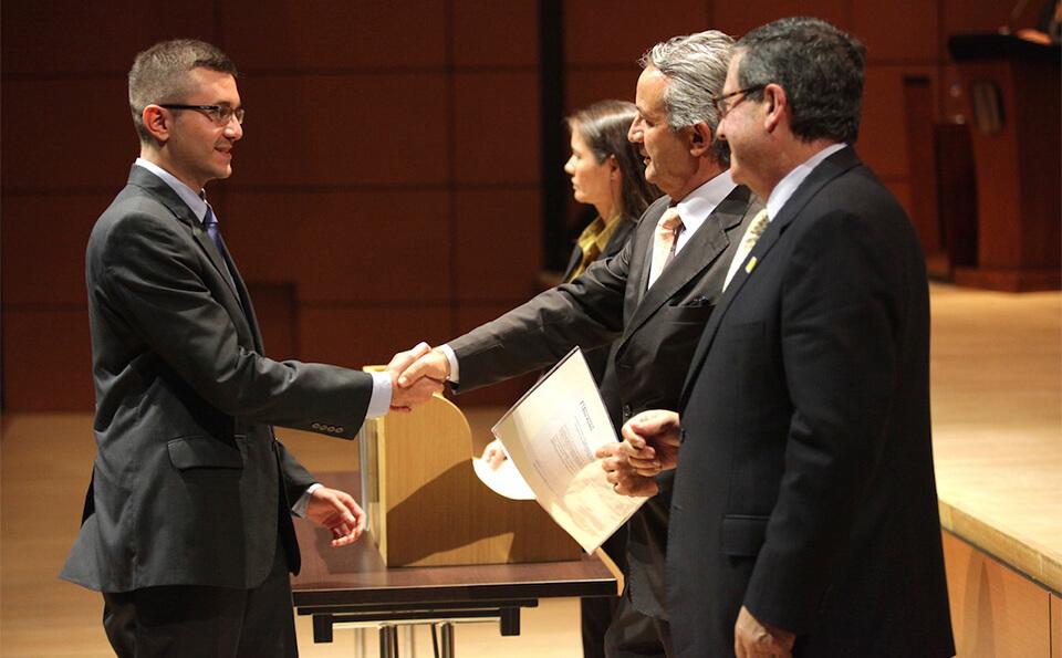 Un hombre de traje recibe da la mano a un hombre mayor en señal de felicitación