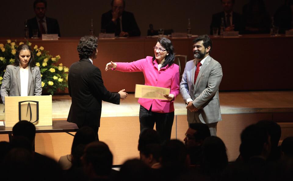 una mujer de blusa fucsia estira su brazo para abrazar y entregar diploma a un hombre vestido con traje