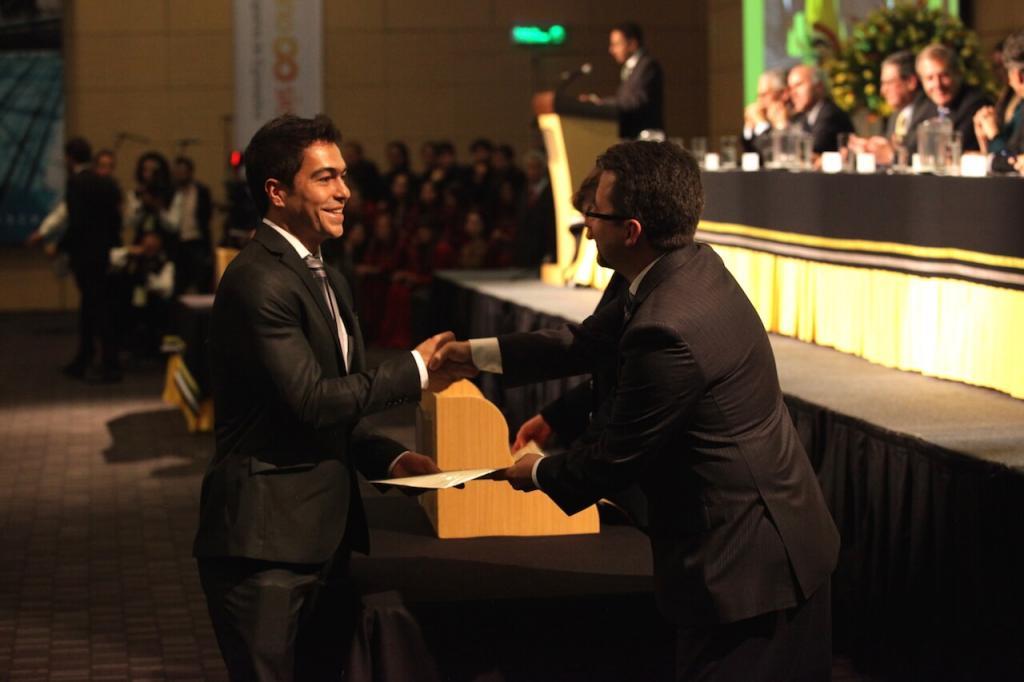 un joven de traje negro da la mano a un hombre que le entrega diploma