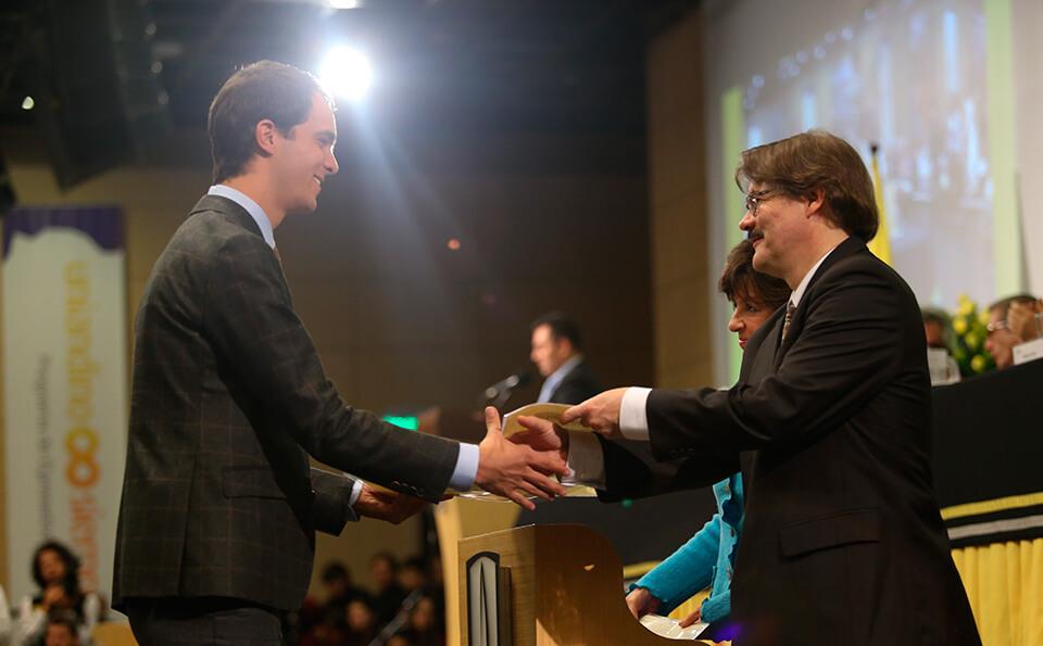 Estudiante uniandino recibiendo su diploma