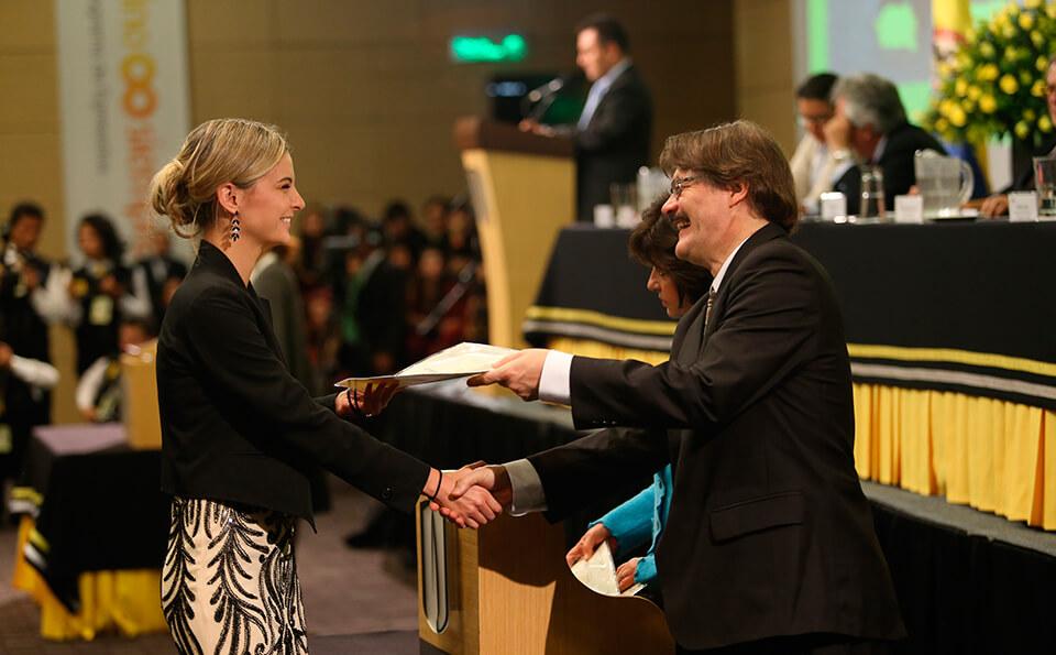 Foto de graduanda recibiendo su diploma de pregrado