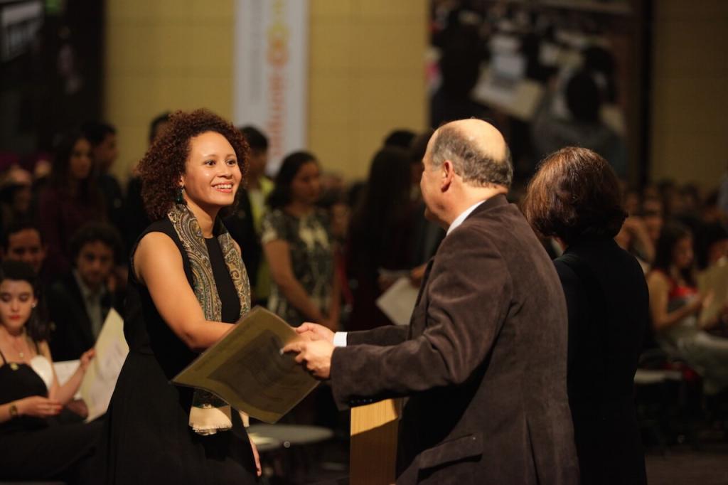 mujer de pelo crespo con pañoleta recibe diploma de grado