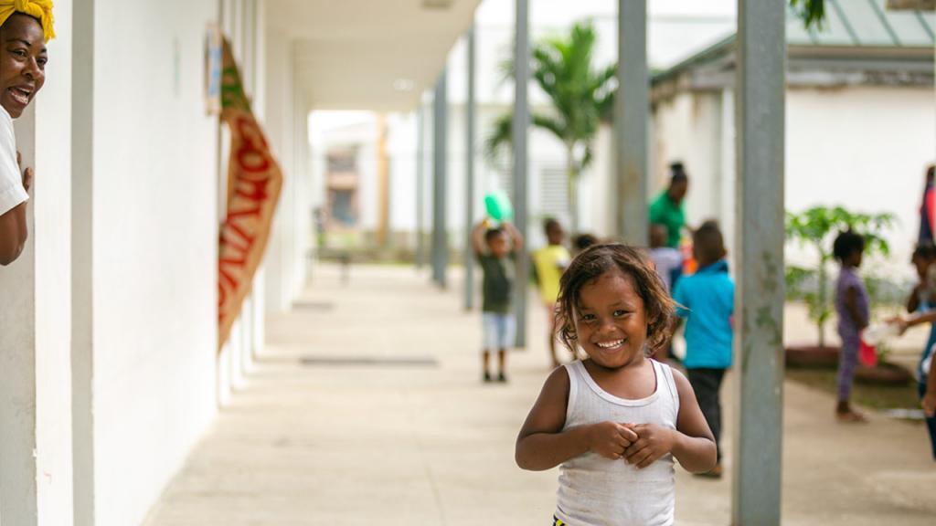 Niña sonriendo en pasillo de escuela