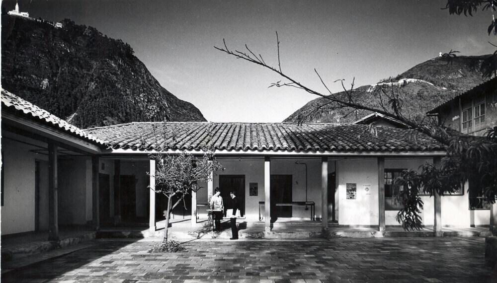 foto antigua en blanco y negro de casa en la universidad de los andes, se ven dos estudiantes frente a una puerta