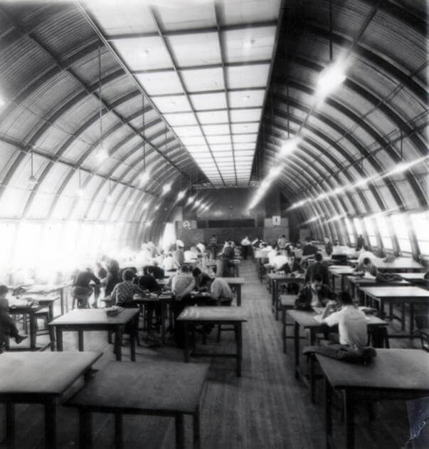 foto antigua y en blanco y negro del espacio llamado la caneca, ahí se ven mesas y estudiantes sentados