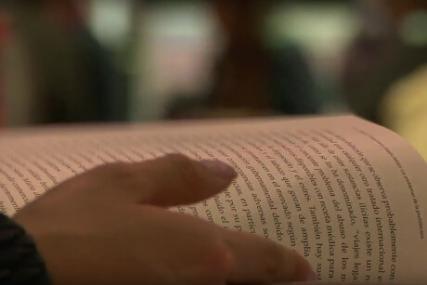Primer plano de una persona leyendo un libro en el estand de Uniandes en la Feria Internacional del Libro de Bogotá