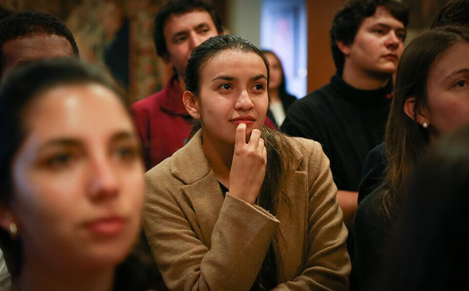 estudiantes en un salón escuchando discurso de celebración por donaciones
