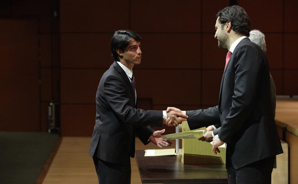 joven estrecha la mano al recibir diploma de un hombre mayor y alto