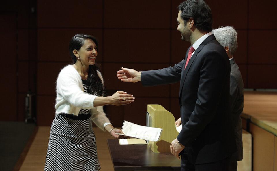 mujer de vestido con puntos estira su mano para estrecharla con un hombre alto
