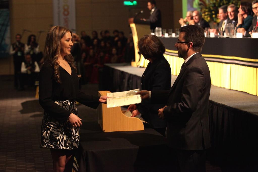 una joven de vestido negro con gris recibe diploma de grado en ceremonia en un auditorio