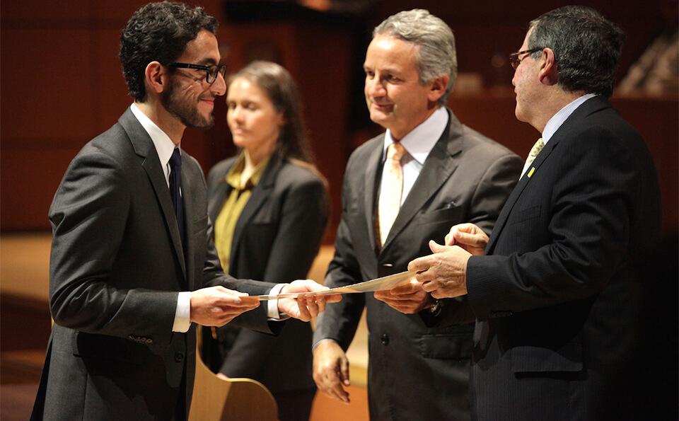 dos hombres mayores entregan diploma de grado a un hombre vestido con traje y gafas negras