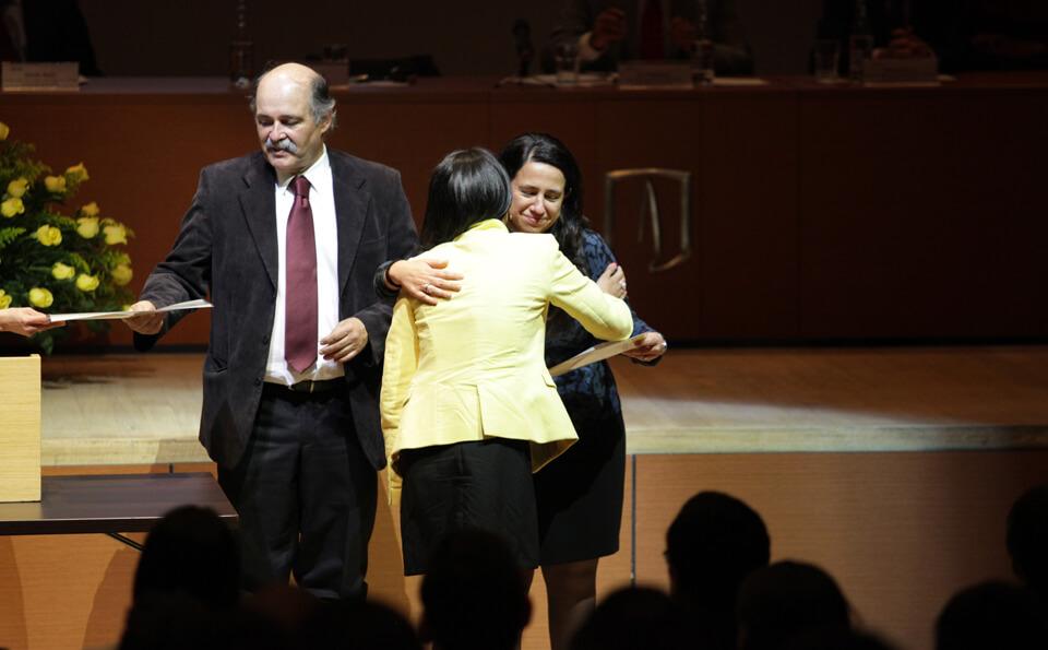 una mujer abraza y entrega diploma a otra mujer en una ceremonia de grados